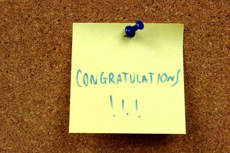 Small sticky note - yellow message on an office cork bulletin board. Congratulations - success notice. Stock Photo - 4822863