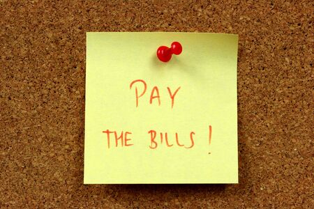 Small sticky note - yellow message on an office cork bulletin board. Bills and expenses - everyday home concept.