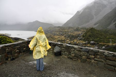 Lonely tourist in yellow plastic raincoat. Rainy weather on a trail near Mt. Cook, New Zealand. photo
