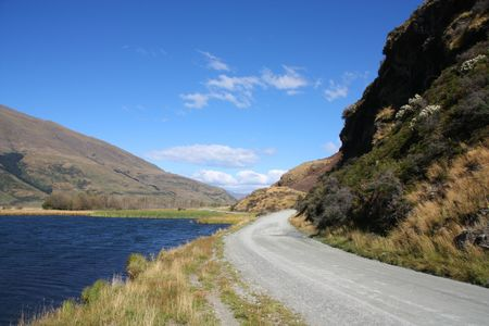 aspiring: Gravel road and lake in Mount Aspiring National Park, New Zealand Stock Photo