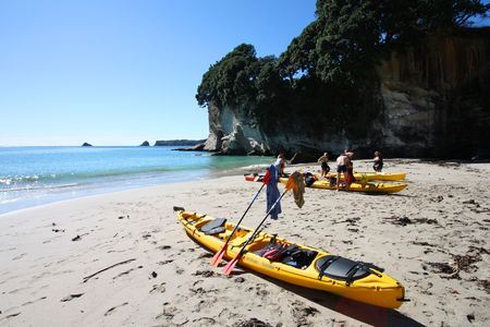 australasia: See kayaking at Cathedral Cove, Coromandel Peninsula. Beautiful beach in New Zealand. Peoples faces have been blurred.