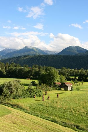 alpen: Countryside in Tirol, Austria. Haystacks, small wooden buildings and mountains in the background. Region of Stubaital and Stubaier Alpen.