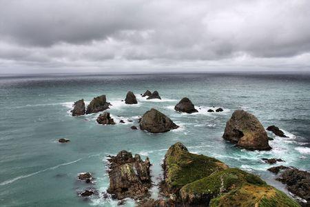 Nugget Point - iconic landform in Otago region of New Zealand. Rainy weather. photo