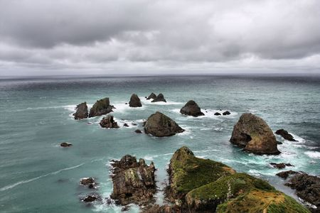 Nugget Point - iconic landform in Otago region of New Zealand. Rainy weather. photo