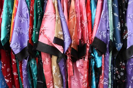 colorful dress: Shopping in Singapore Chinatown. Beautiful, colorful silk dresses. Oriental clothes. Background texture.