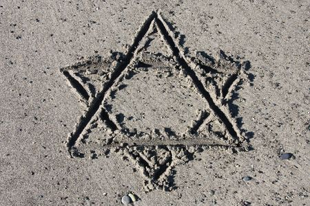 Hebrew symbol - Star of David drawing on sand. Jewish symbology. photo