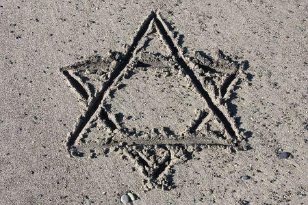 Hebrew symbol - Star of David drawing on sand. Jewish symbology. photo