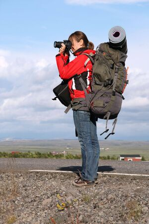 backpackers: Female tourist taking photos. Girl backpacker, travel photographer in Iceland.