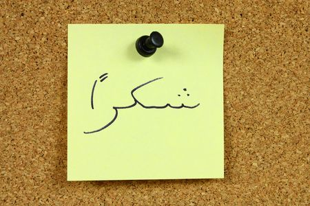Yellow small sticky note on an office cork bulletin board. Word shukran in Arabic, which means thank you. photo