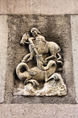 Small bas-relief statuette in Barcelona, Spain. Saint George slaying a dragon. photo
