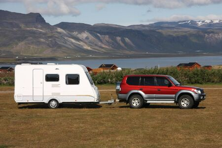 Parked red generic vehicle with a camping trailer. Campground in Snaefellsnes peninsula, Iceland.