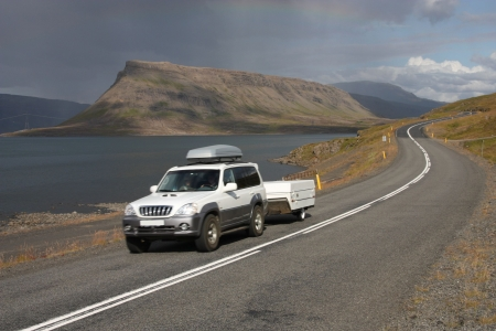 scenic drive: Generic SUV with a trailer in motion next to Hvalfjordur fiord in Iceland
