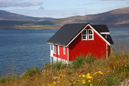 nordic nature: Small red generic home next to Hvalfjordur fiord in Iceland. Typical Nordic residential architecture. Stock Photo