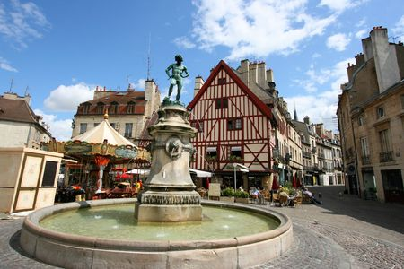 Famous fountain, characteristic houses and colorful carousel in Dijon, Burgundy, France. Place Francois Rude. Stock Photo - 5883049