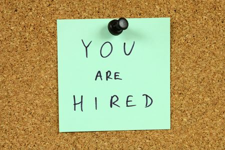 hired: Green small sticky note on an office cork bulletin board. You are hired message. Career success, new employment. Stock Photo