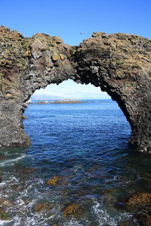 rock arch: Amazing natural rock arch in Arnarstapi, Snafellsnes peninsula, Iceland. Faxafloi bay.