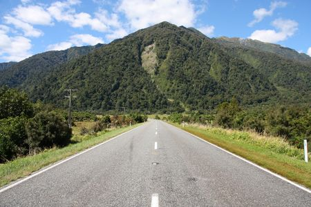 temperate region: Straight road and mountains in green New Zealand. Temperate rainforest in West Coast region.