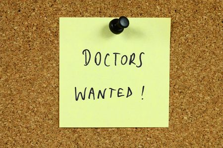 Yellow sticky note pinned to an office notice board. Doctors wanted - employment and medical career recruitment message. Stock Photo - 6154558
