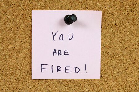 Pink sticky note pinned to an office notice board. You are fired - financial crisis, unemployment, career information. Banque d'images - 6178606