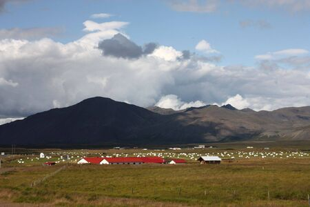 Red roofed farmhouse in Iceland. Grassy plains and mountains. Stock Photo - 6189521