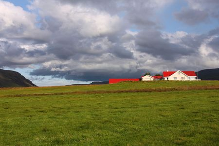 Beautiful red roofed farm in Iceland. Stormy clouds weather. Stock Photo - 6189536