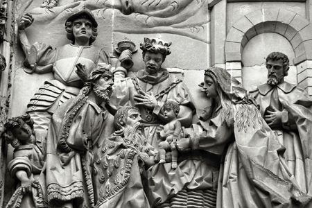Three wise men or three kings visit the newborn Jesus Christ. They bear gifts of gold, frankincense, and myrrh. Sculpture above the Puerta del Nacimiento of Salamanca Cathedral. photo