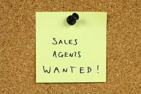 Yellow sticky note pinned to an office notice board. Sales agents wanted - employment and career recruitment message. Stock Photo - 6189676