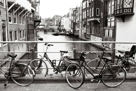 dordrecht: Bicycles next to water canal in Dordrecht, Netherlands. Black-white atmostpheric photo.