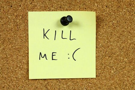 suicidal: Yellow sticky note pinned to an office notice board. Kill me - suicidal, depression message. Euthanasia concept. Stock Photo