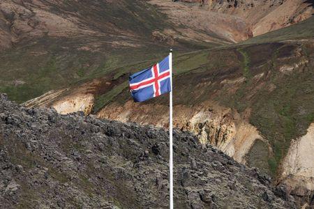 felsic: Icelandic flag. Beautiful mountains in Iceland. Famous volcanic area with rhyolite rocks - Landmannalaugar. Lava field black rocks.