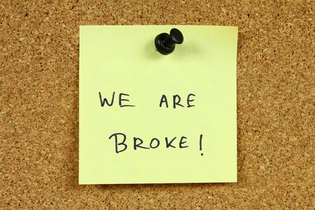 Yellow sticky note pinned to an office notice board. We are broke - bankruptcy, unemployment and financial problems message. Stock Photo - 6244594