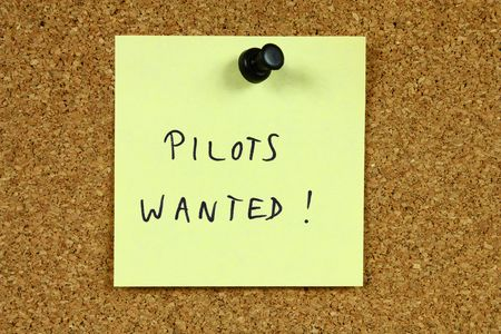 Yellow sticky note pinned to an office notice board. Pilots wanted - airline employment and aviation career recruitment message. Stock Photo - 6310412