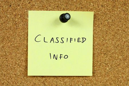 Yellow sticky note pinned to an office notice board. Classified info - secred government information concept. Stock Photo - 6311789