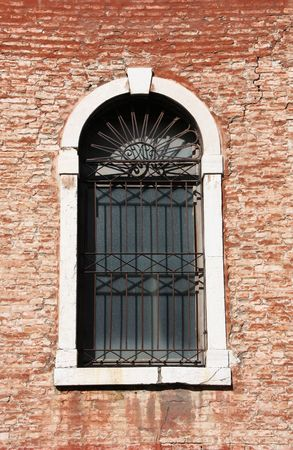 Old building in Venice, Italy. Vintage window with rusty decorative bars. photo