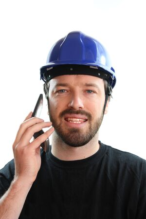 Construction worker in blue hard hat, talking on the phone. Caucasian male in his 20s. Young man portrait. photo