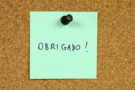 portugese: Green sticky note pinned to an office notice board. Obrigado - thank you in Portugese.