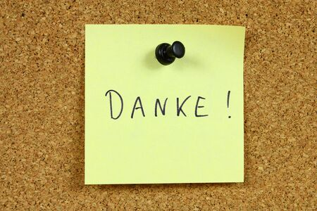 Yellow sticky note pinned to an office notice board. Danke - thank you in German language. photo