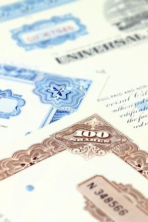 100 shares. Old stock share certificate. Vintage scripophily objects. Shallow depth of field. photo