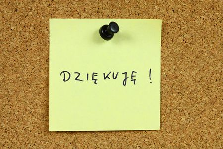 Yellow sticky note pinned to an office notice board. Dziekuje - thank you in Polish language. photo