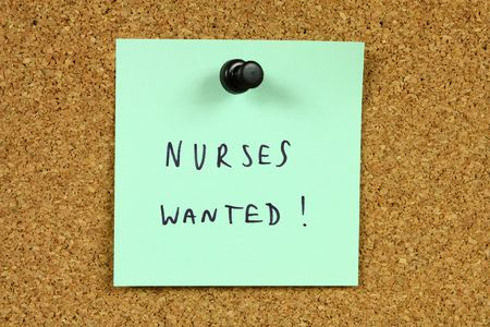 postit: Green sticky note pinned to an office notice board. Nurses wanted - medical career opportunity and recruitment information. Stock Photo