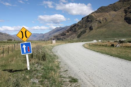 aspiring: Gravel road and a sign in Mount Aspiring National Park, New Zealand