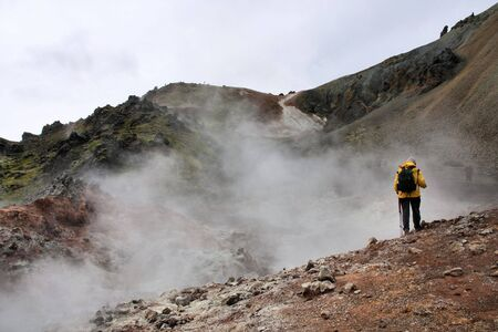 felsic: Iceland. Tourist and a steaming crater. Famous volcanic area with rhyolite rocks - Landmannalaugar.