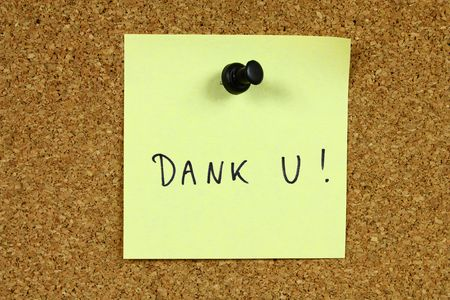 Yellow sticky note pinned to an office notice board. Dank u - thank you in Dutch. photo
