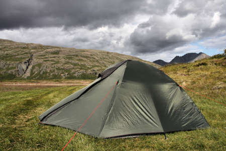 imminent: Tent in Lonsoraefi - desolate hiking area in Iceland. Summer camping. Stormclouds - overcast sky.