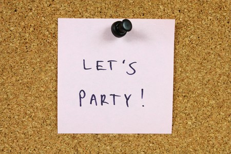 lets: Pink sticky note pinned to an office notice board. Lets party - anniversary celebration party invitation.