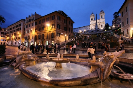ROME - MAY 10: Tourists strolling on May 10, 2010 in Rome, Italy. Piazza di Spagna with its fountain and Spanish Steps is one of the most iconic city squares in the world and one of Italys top tourism destinations.