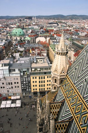 architectural architectonic: Vienna aerial view - old town down there and financial district skyscrapers in the background. Stephansdom cathedral roof in the foreground.