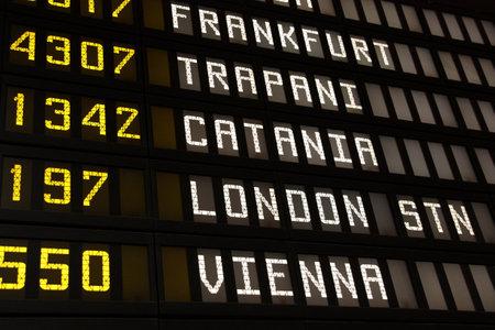 cronograma: Placa de salida en un aeropuerto en Italia. Vuelos a Frankfurt, Trapani, Catania, Londres y Viena