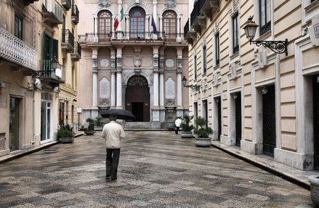 Trapani, Sicily in Italy. Old town and anonymous person with umbrella in the rain. photo