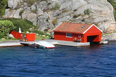 kristiansand: Norway - Skjernoy island in the region of Vest-Agder. Red fishing boat garage. Stock Photo